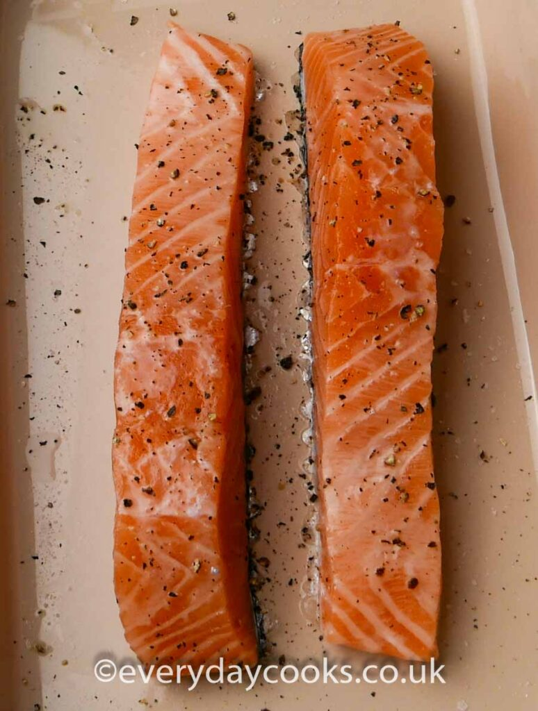 Two raw salmon fillets in a gratin dish