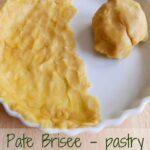 A white quiche dish half covered in pastry