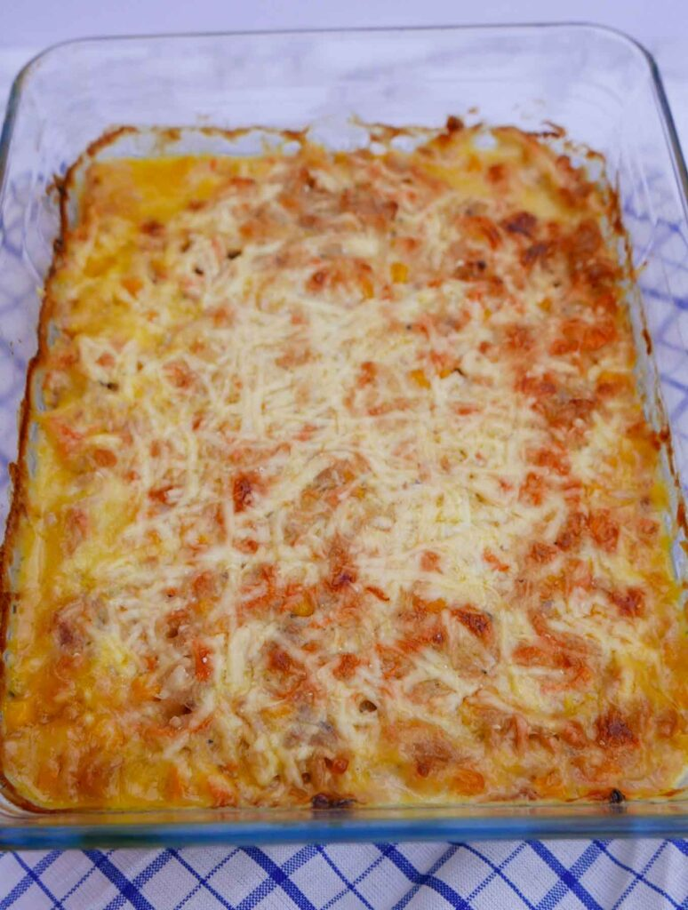 Tuna Pasta Bake in a rectangular glass casserole dish of tuna pasta bake with melted cheese on top.