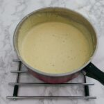 Cheese sauce in a red saucepan - ready to eat.