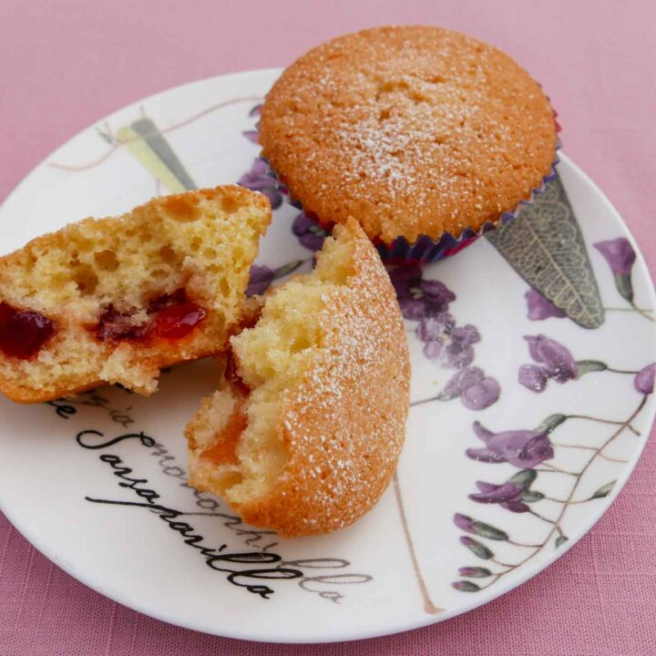 Two jammy buns on a small flowered plate. One bun is split open to see the strawberry jam inside.