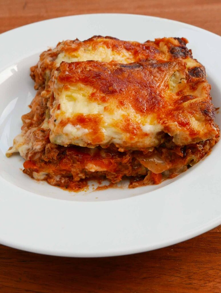 A slice of everyday lasagne in a white bowl, showing layers of meat, pasta and cheese sauce topped with melted cheese.