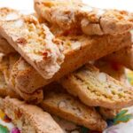 Apricot and almond biscotti pile up on a flowered plate.