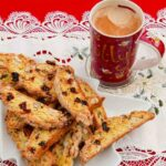 Cranberry and Hazelnut Biscotti on a white plate with a mug of coffee