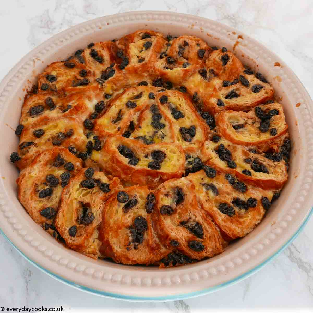Brioche Bread and Butter Pudding. Slices of chocolate brioche with currants in a custard in a round pie dish