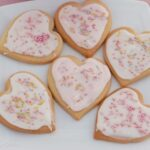 Heart-shaped Valentine biscuits with white or pale pink icing and pink, gold and silver sprinkles