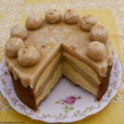 Orange Simnel Cake with a slice removed showing the layer of marzipan inside