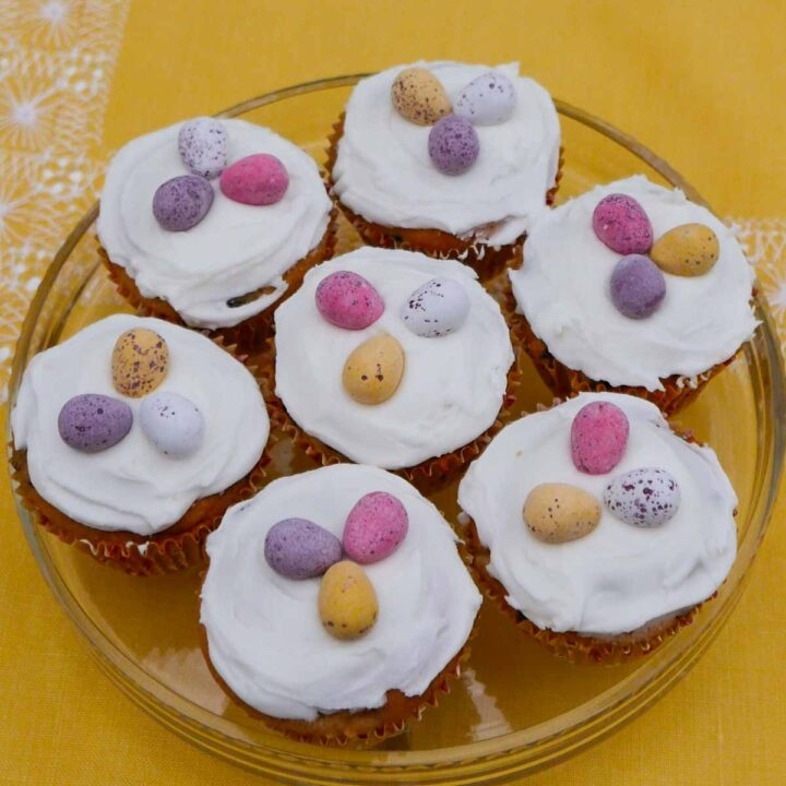Simnel Cupcakes on a glass dish decorated with icing and chocolate eggs