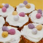 Simnel cupcakes topped with icing and chocolate eggs