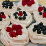 7 Pavlova nests, filled with cream, raspberries and blueberries, on a plate