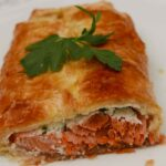 Salmon en Croûte - cut to show salmon baked in puff pastry with a parsley garnish.