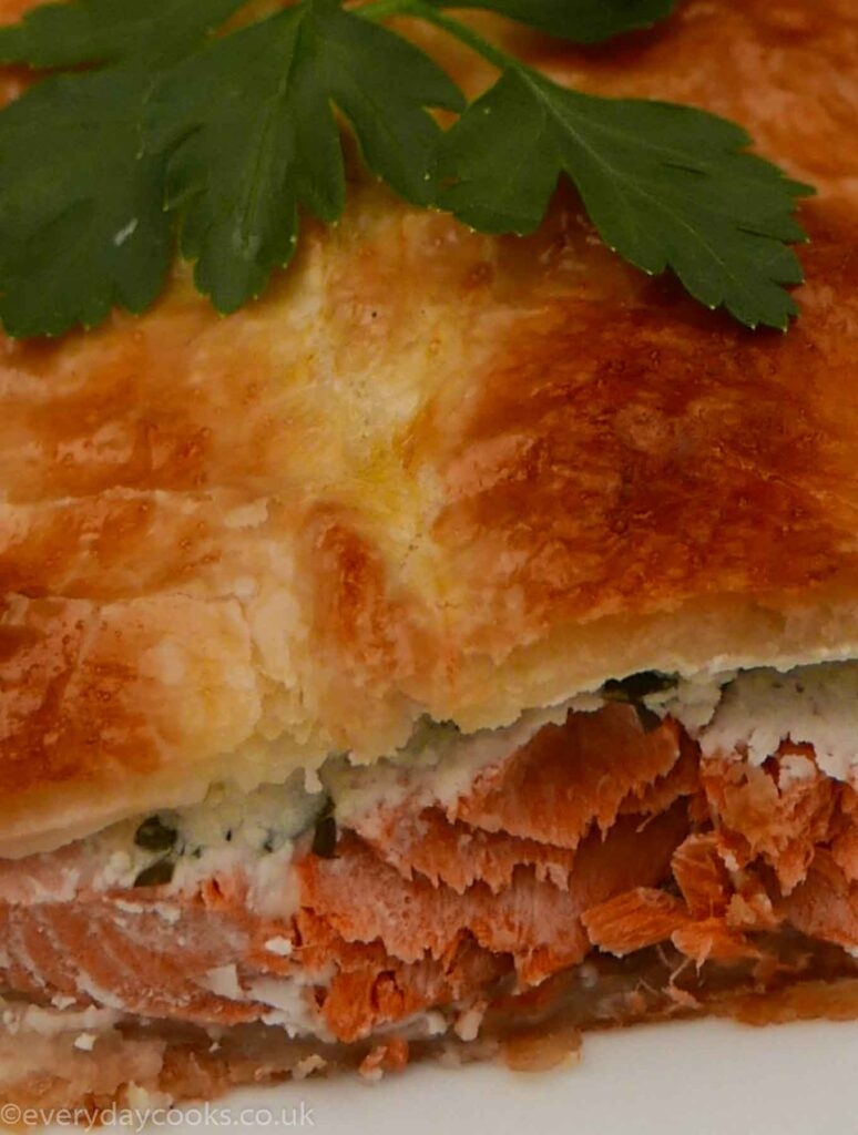 Salmon en Croûte - a slice of salmon baked in puff pastry with a parsley garnish.