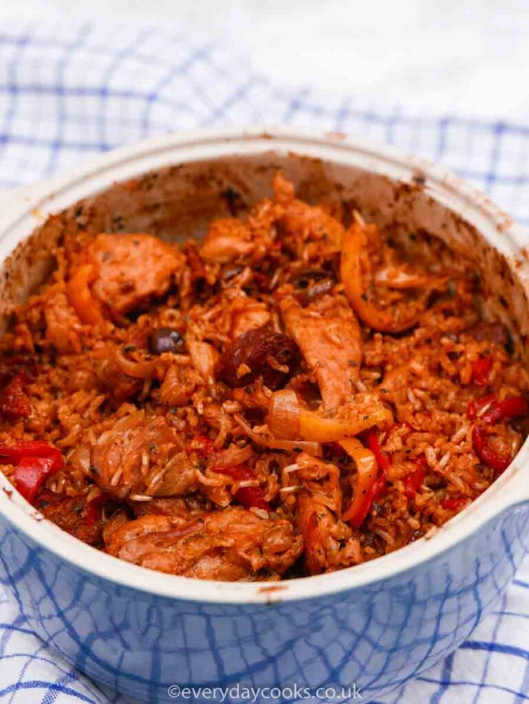 Spanish Chicken and Rice in a blue casserole dish on a blue checked tea towel