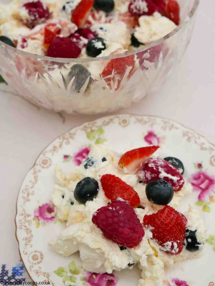 A serving of Eton Mess on a plate with the serving dish behind.
