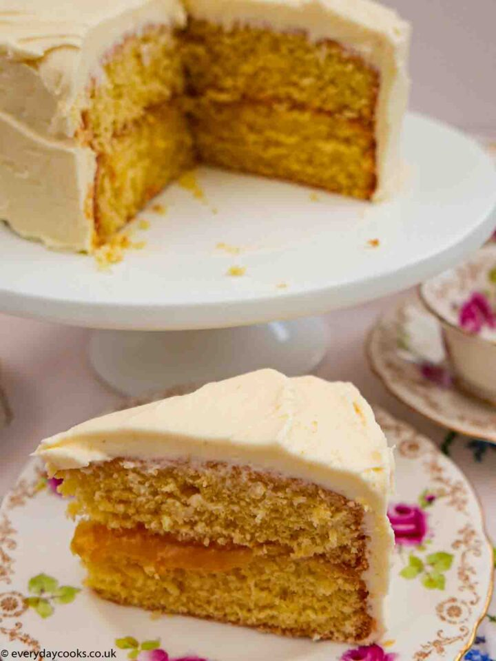 A slice of Lemon and Elderflower Cake on a rose-patterned plate with the rest of the cake on a white cake stand.