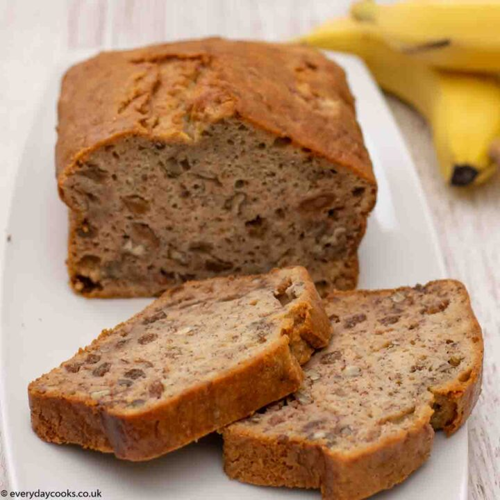 Two slices of Banana Loaf on a white plate with the rest of the cake and 2 bananas in the background