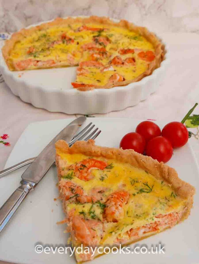 A Salmon and Prawn Quiche in a white china dish with a slice on a white plate