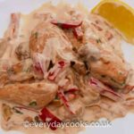 Chicken in Mustard and Cream Sauce with mushrooms and red pepper on a white plate with a wedge of lemon.
