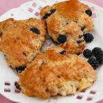 3 Blackberry Scones on a white plate with blackberries.