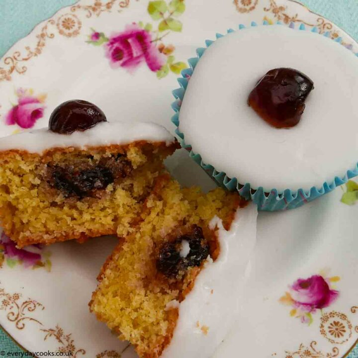 One whole and one cut Cherry Bakewell Cupcakes on a plate.