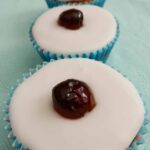 Three Cherry Bakewell Cupcakes on a cloth