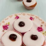 Three Cherry Bakewell Cupcakes on a plate with three in the background