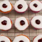 Cherry Bakewell Cupcakes on a wire cooling rack