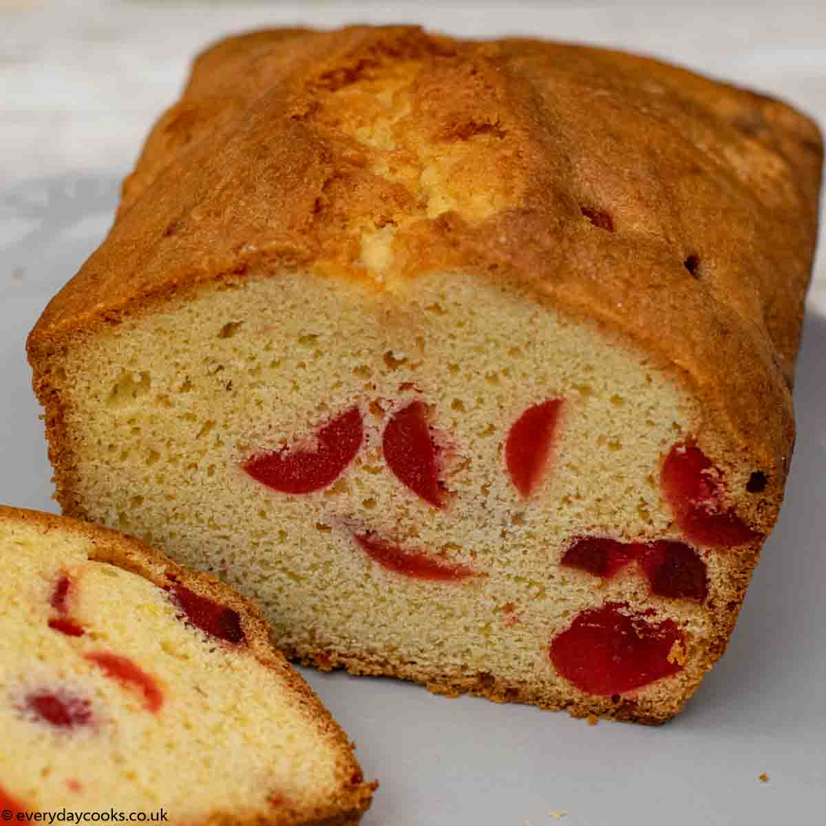 Cherry Cake on a grey plate with part of a slice of cake to the left