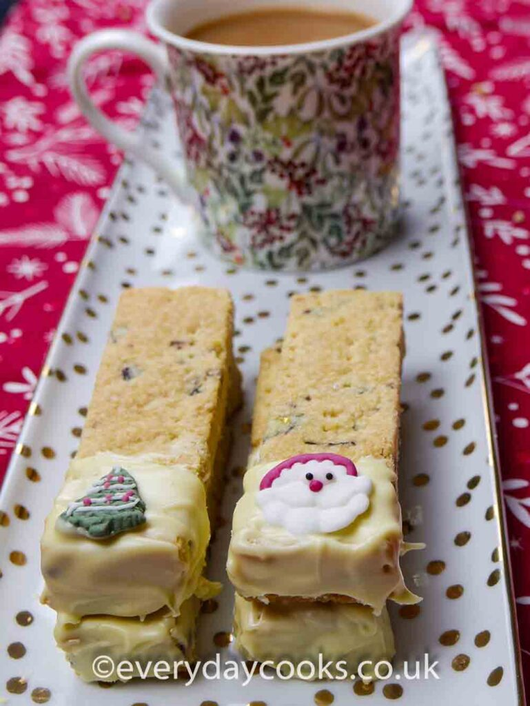 4 pieces of Christmas Shortbread part coated in white chocolate, on a china plate.