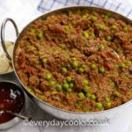 Keema in a stainless steel serving dish with Indian condiments