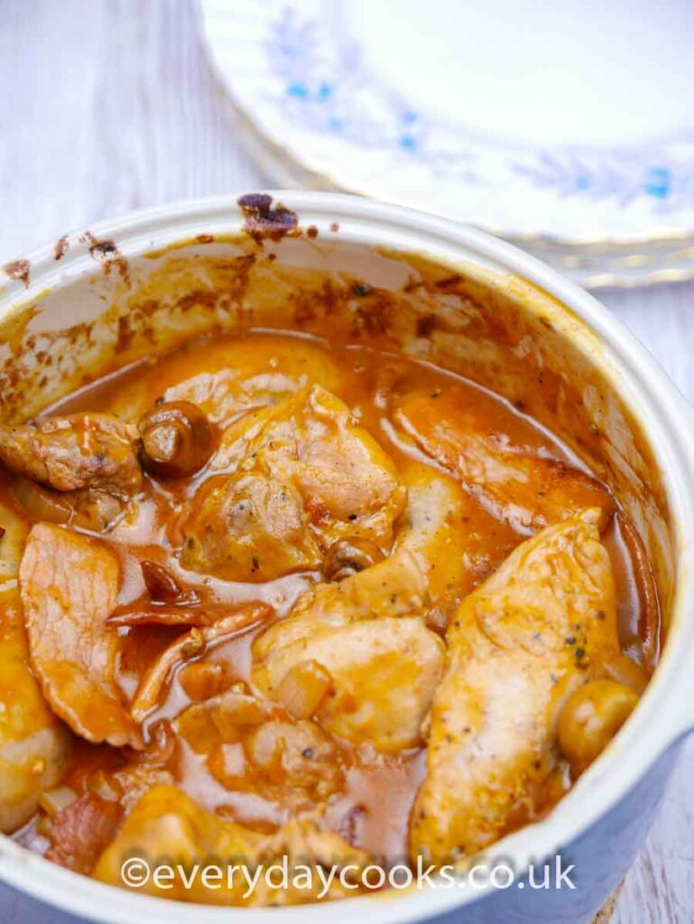 Chicken Chasseur in a blue casserole dish with plates in the background