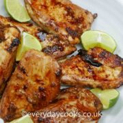 Pieces of Ginger Lime Chicken in a white dish with a quartered lime