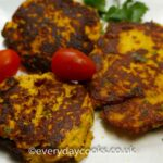 3 Smoked Mackerel Fishcakes on a plate with tomatoes