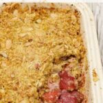 Strawberry Crumble in a pie dish with a portion missing