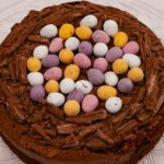 Chocolate Easter Nest Cake topped with chocolate cream and mini eggs