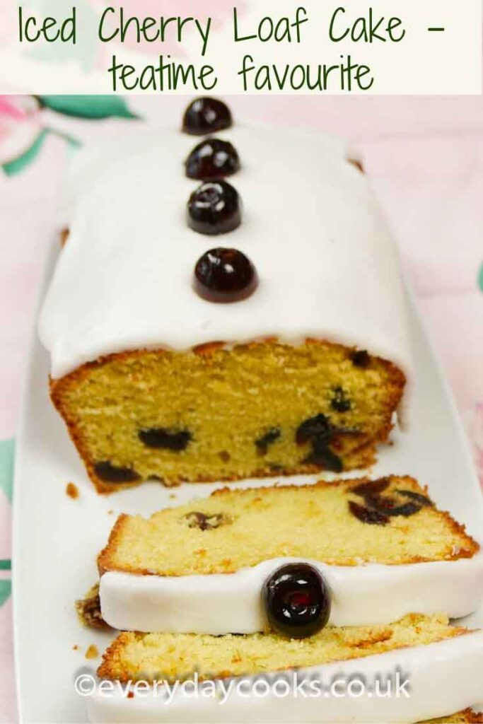 Iced Cherry Cake with a slice cut, on a white plate.