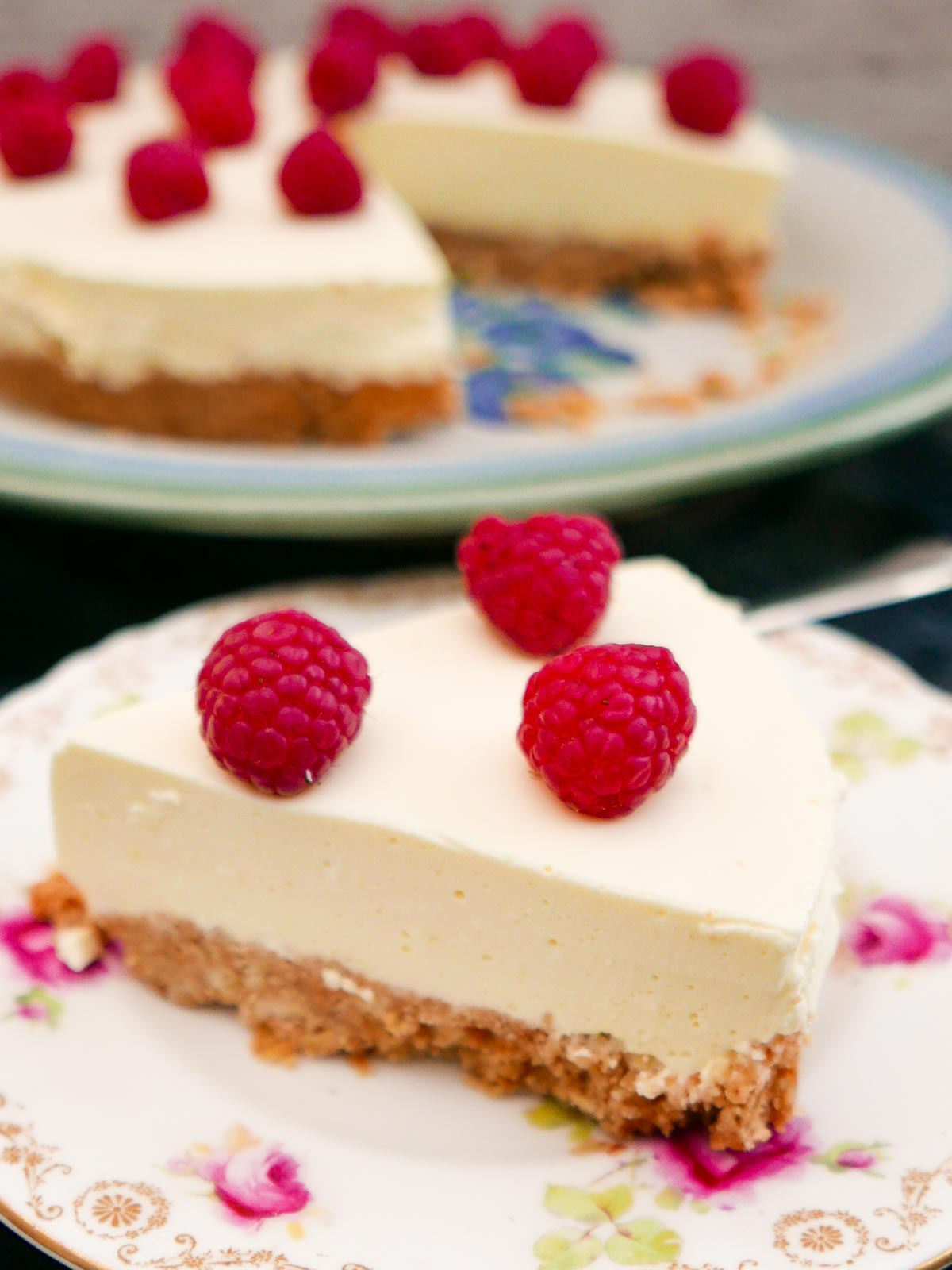 Slice of Easy Lemon Cheesecake with the rest of the cheesecake in the background.