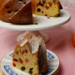 Fruit Bundt Cake on a white plate with a slice on a blue plate. With 3 oranges on a pink table cloth