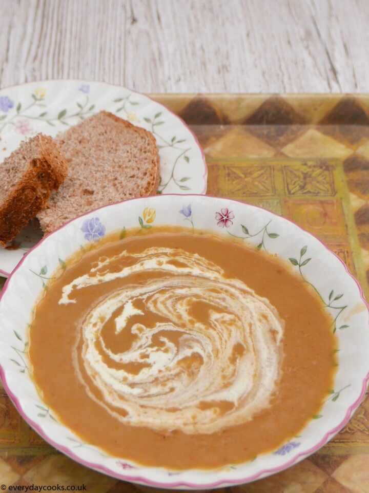 Christmas vegetable soup in a bowl with a piece of bread on a plate.