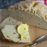 Half a loaf of Easy No Yeast Bread with 2 slices, butter and butter knife on a beechwood board.