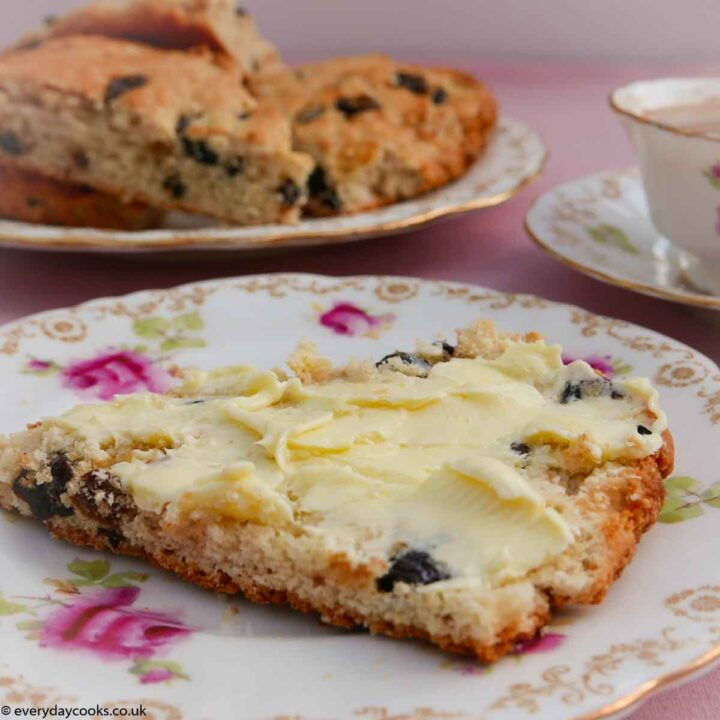 A slice of buttered fruit tea scone with a plate of scone a nd a cup of tea in the background. All on a pink tablecloth and on old-fashioned china with pink roses and a gold border.