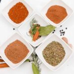 5 Herb and Spice Mixes in small white bowls on a white plate