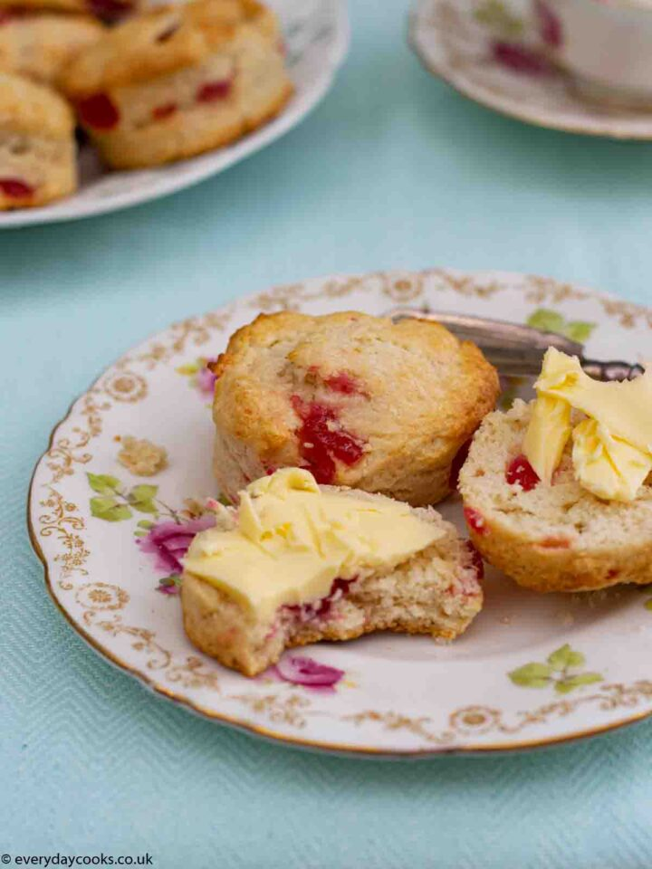 A Cherry Scone cut in half with butter and a whole scone on a patterned plate. More scones and a teacup int he background