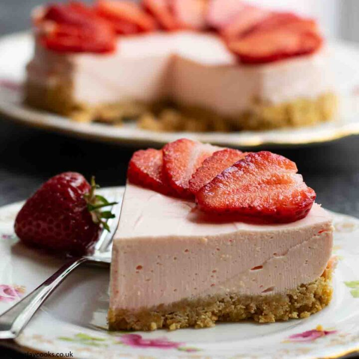 A slice of Easy Strawberry Cheesecake topped with sliced strawberries on a patterned plate on a black worktop. The rest of the cheesecake is in the background.
