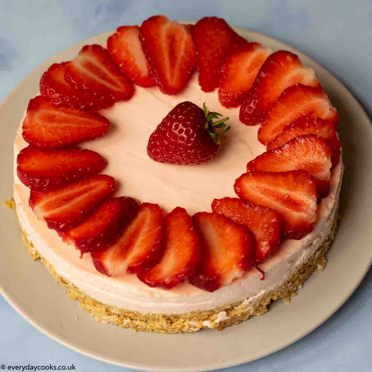 Easy Strawberry Cheesecake topped with sliced strawberries on a grey plate on a blue worktop.