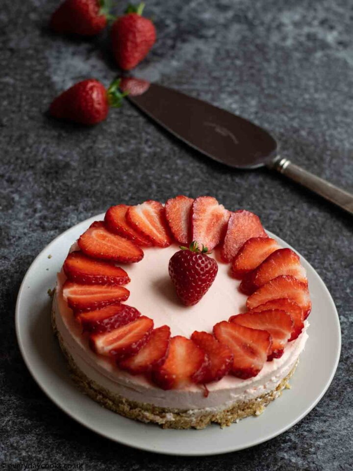 Easy Strawberry Cheesecake topped with sliced strawberries on a grey plate on a black worktop. 3 strawberries and a cake knife in the background.