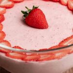 Easy Strawberry Mousse decorated with strawberry slices, in a glass bowl on a wooden table