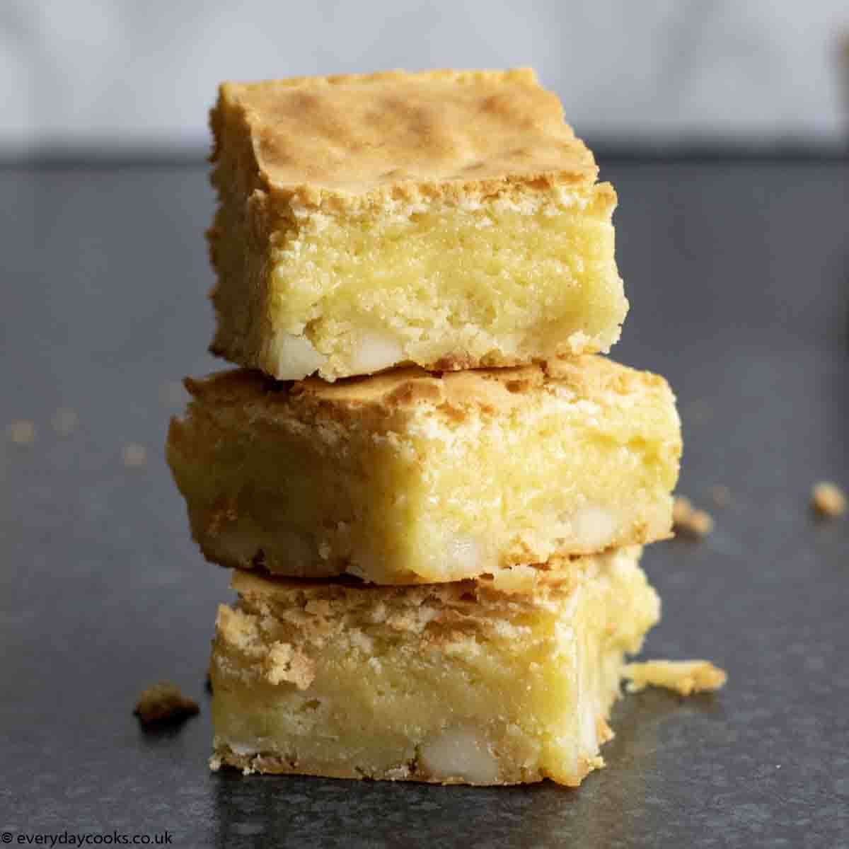 Stack of 3 White Chocolate Brownies on a dark worktop