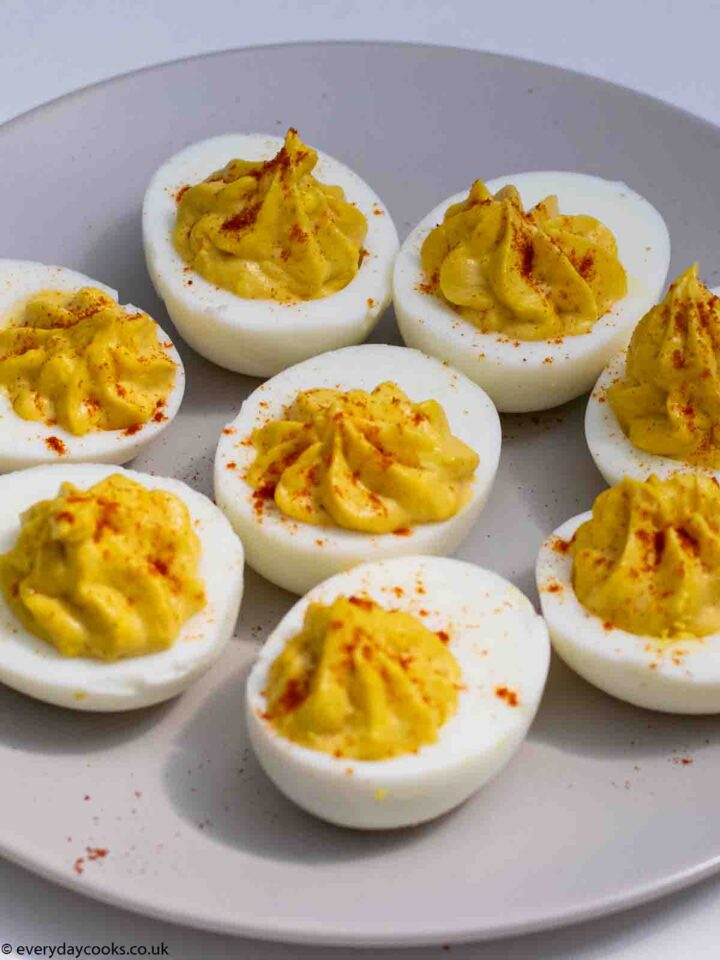 Eight Devilled Eggs halves, sprinkled with red paprika, on a grey plate