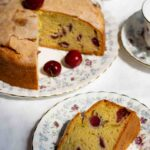 Fresh Cherry Cake, with a slice removed, on a patterned plate. A slice of cake on a small plate with a cup of tea and a bowl of cherries